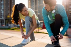woman and man tying running shoes using exercise to recovery