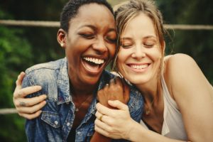 two women hugging and laughing during mindfulness meditation therapy