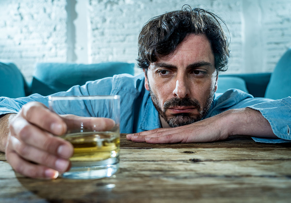 a man staring at a whiskey glass wondering Am I an alcoholic