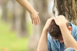 hand reaching out to crouched man showing how to help an addict with addiction treatment in new hampshire