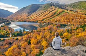 woman sitting on a mountain overlooking the fall scenery outside of New Hampshire addiction treatment centers