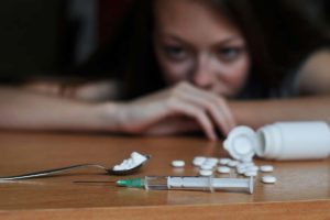 woman in the stages of addiction recovery leaning on table looking at drug paraphernalia needing addiction recovery center NH